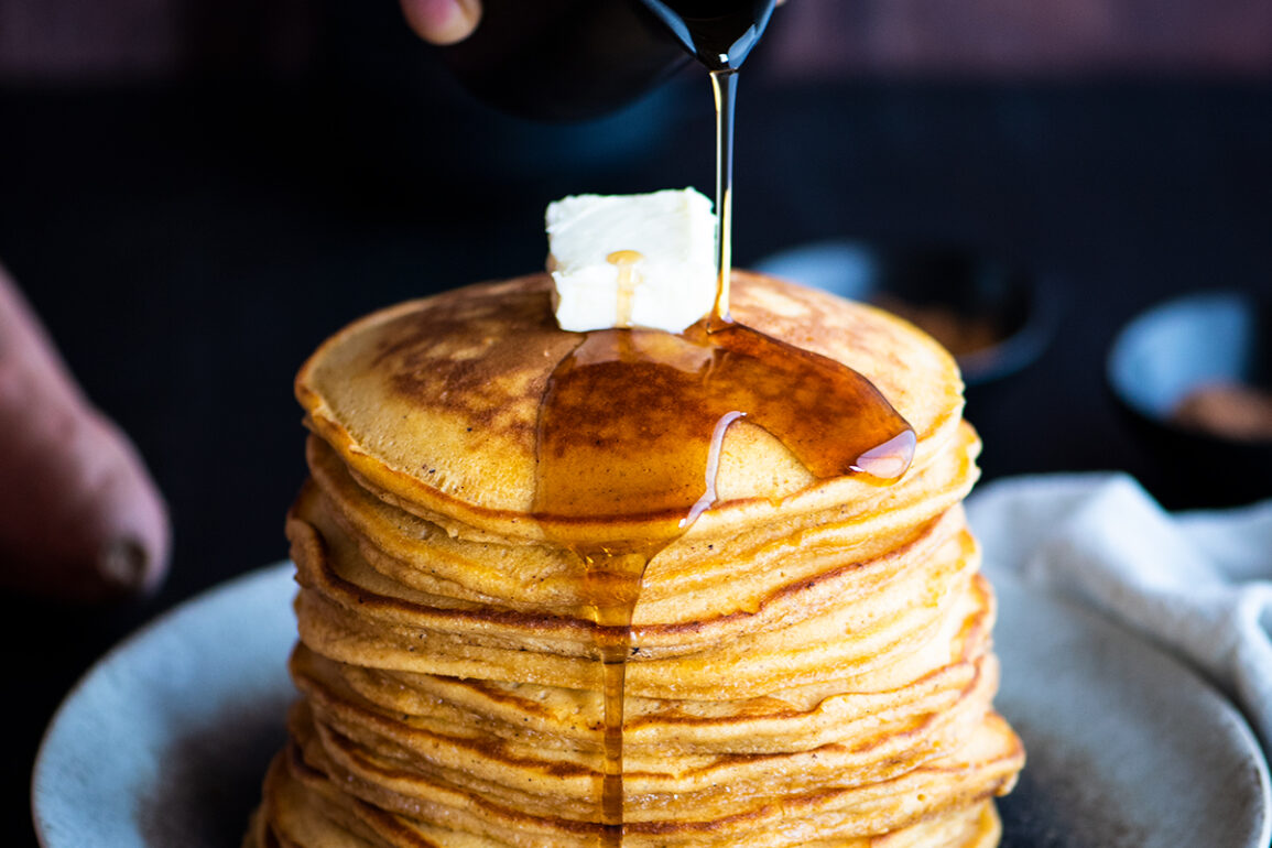 Pouring syrup on a stack of sweet potato pancakes