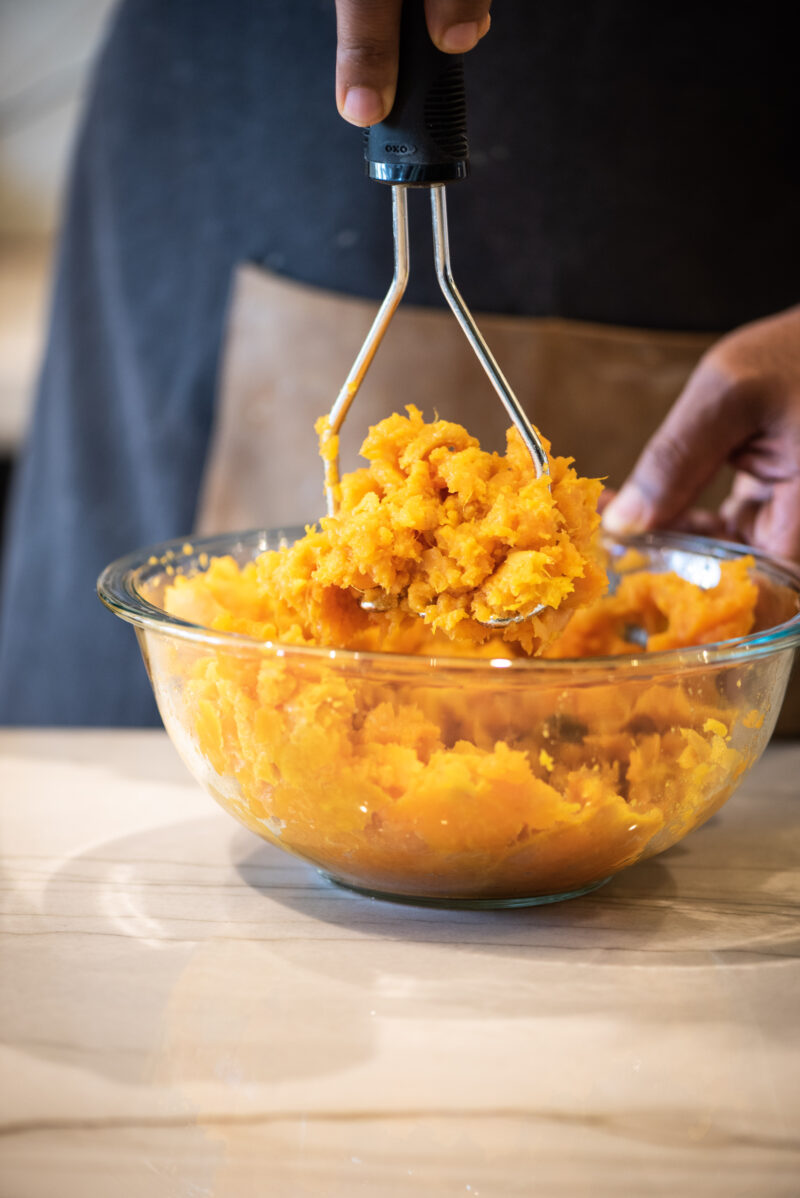 Mashing sweet potatoes using a potato masher