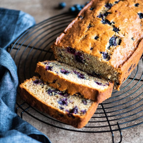 sliced blueberry banana bread on a cooling rack