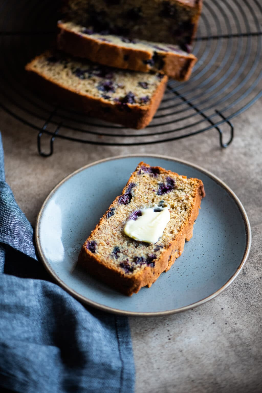 slice of blueberry banana bread with butter on top