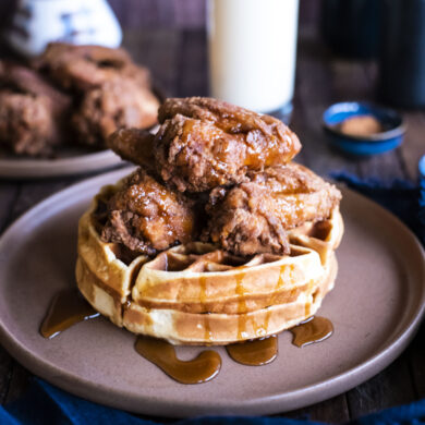 front picture of chicken and waffles on table with cup of eggnog