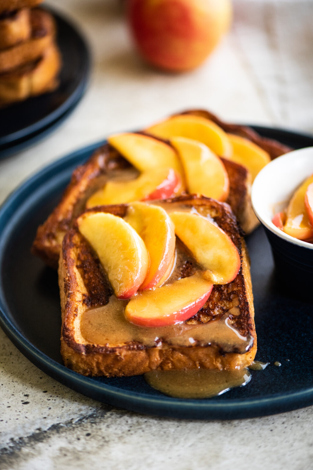 plate of french toast topped with apples