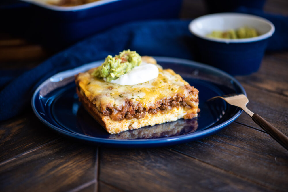 Low-Carb Tex-Mex Casserole topped with sour cream and guacamole
