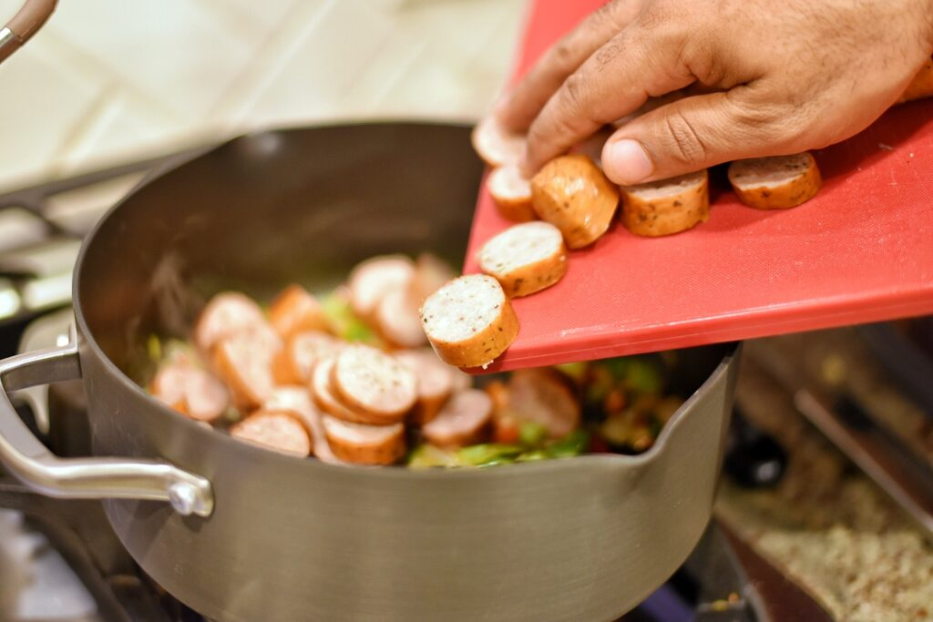Adding the sliced chicken sausage to the pan