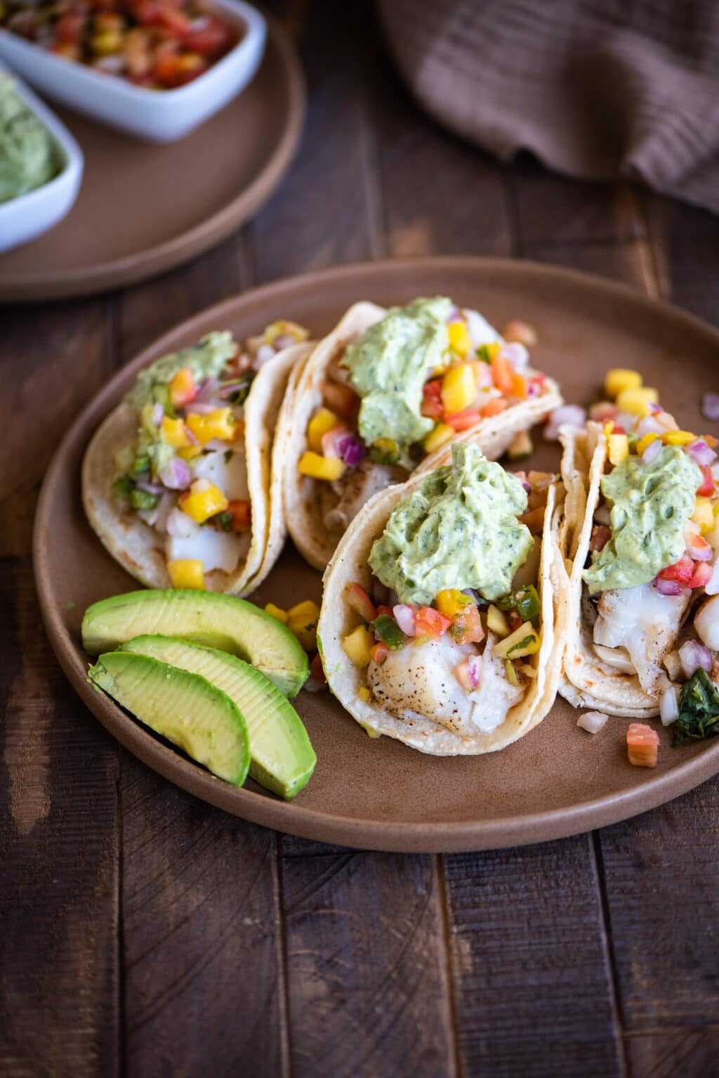 grilled fish tacos on a plate with sliced avocado