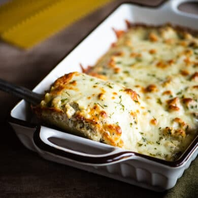 Taking a lasagna roll from the baking dish