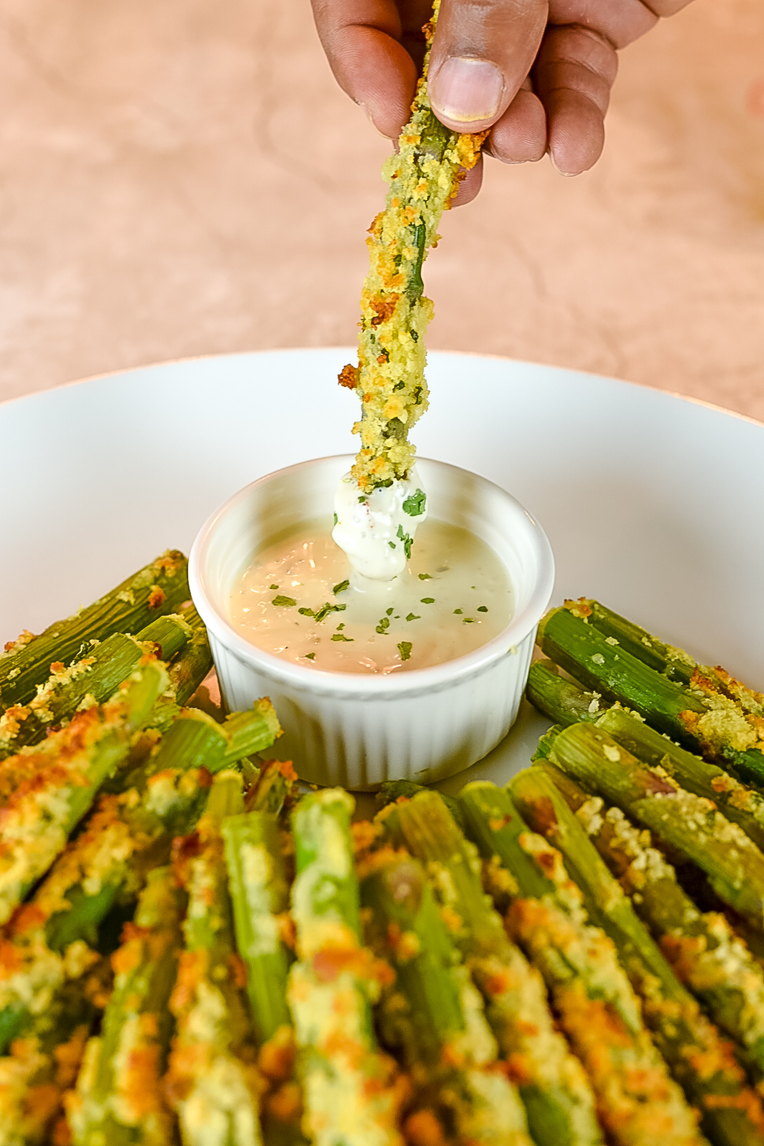Dipping Parmesan Crusted Asparagus Spears in ranch dressing.