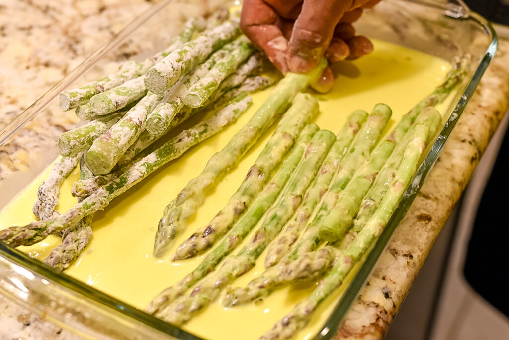 Dipping trimmed asparagus spears is egg batter.