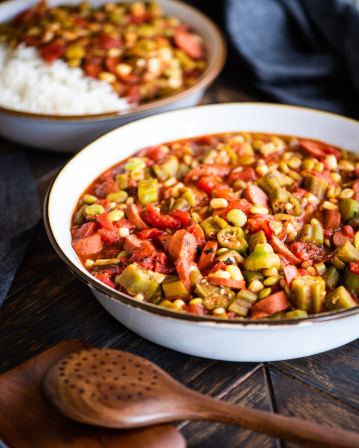 large bowl of stewed okra with a side portion of stewed okra