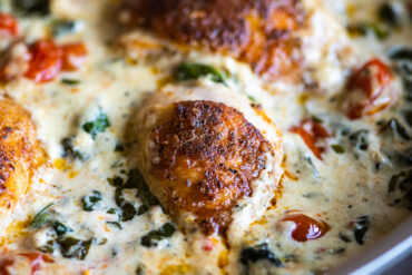 close up up a chicken drumstick in a creamy tuscan sauce with spinach and cherry tomatoes