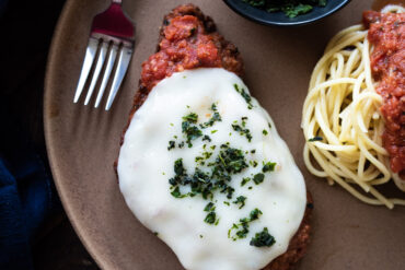 Plated chicken parmesan with a side of spaghetti and tomato sauce