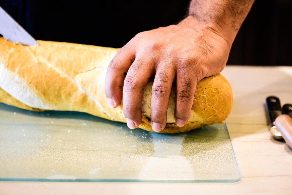 Cutting french bread for Bananas Foster French Toast Casserole.