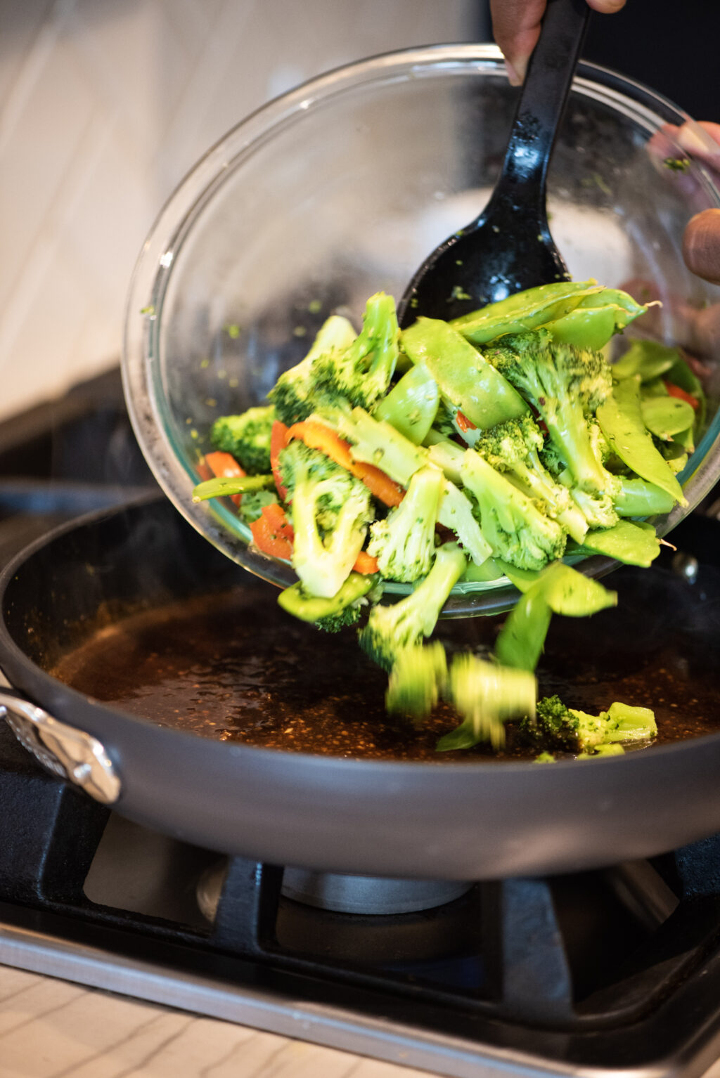 Adding fresh vegetables to pan