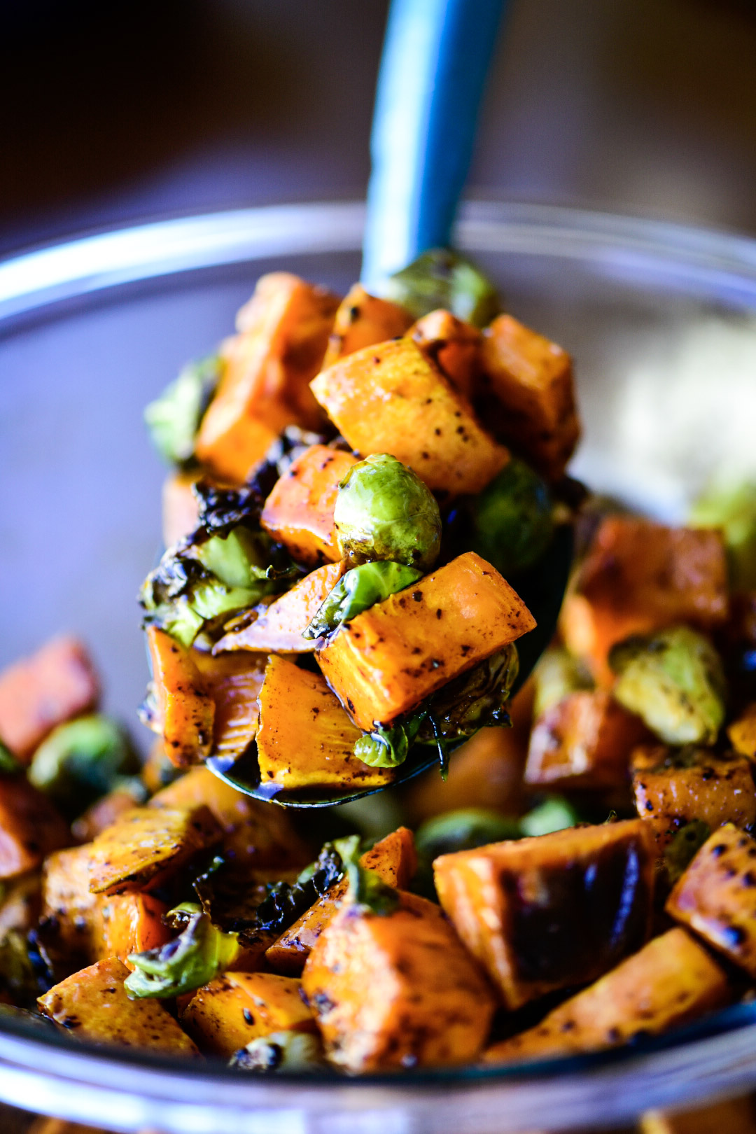 tossing sweet potatoes and Brussels sprouts in honey-balsamic sauce