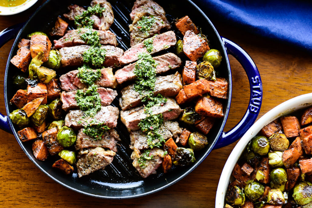 Overhead shot of sliced new york strip loin with chimichurri sauce