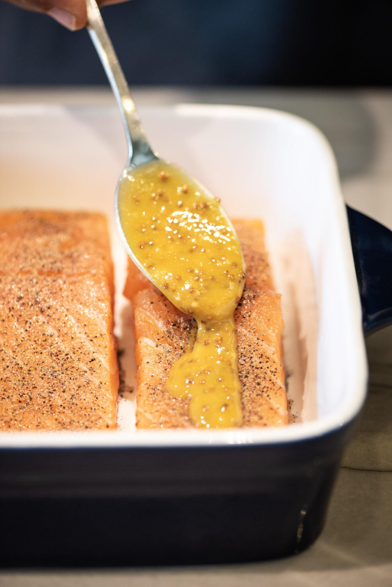 Adding honey-mustard glaze to salmon