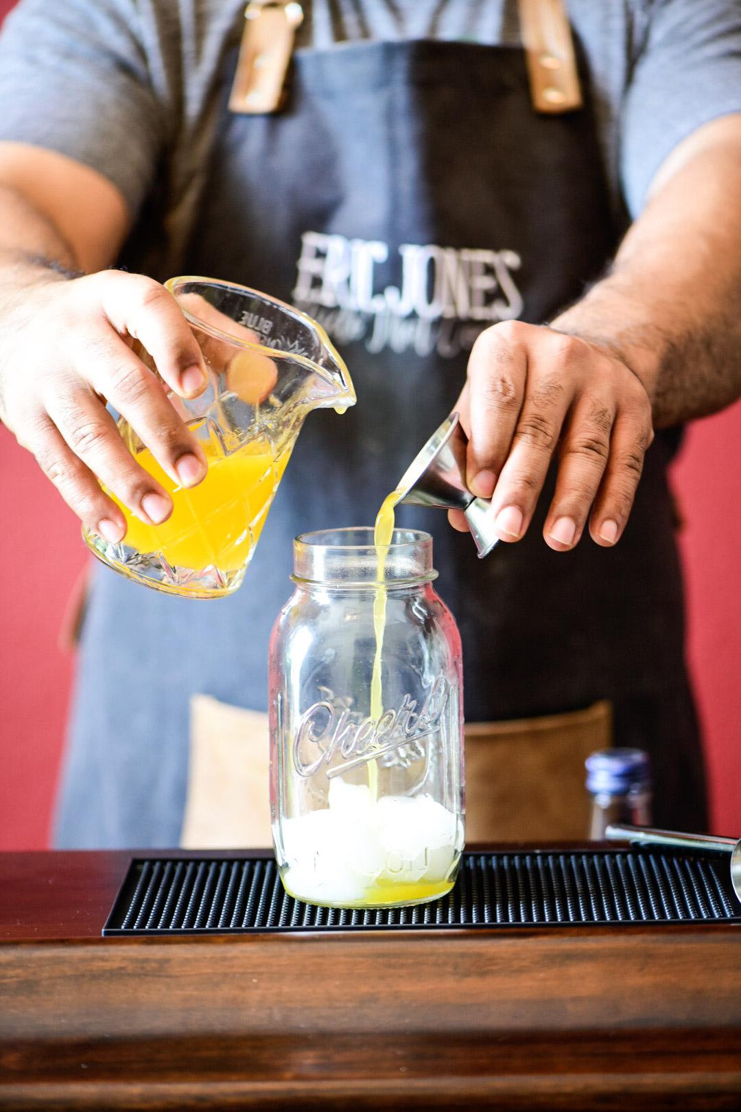 Adding fresh mandarin juice to cocktail shaker for Mandarin Orange Crush Cocktail