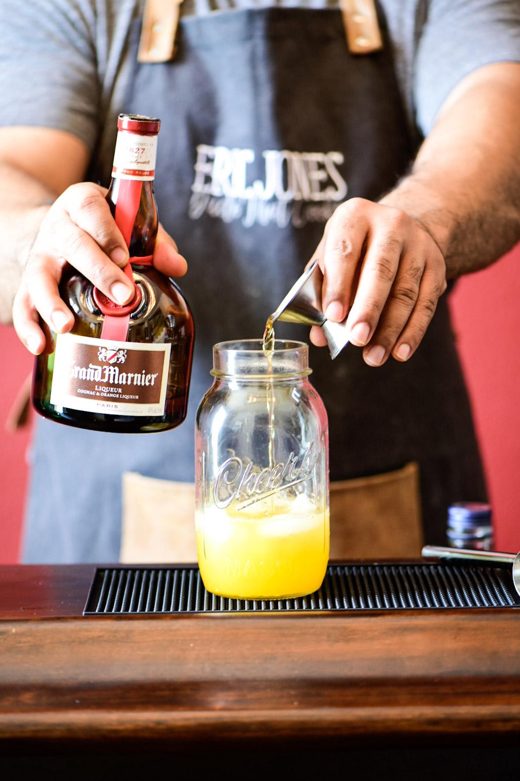 Adding Grand Mariner to cocktail shaker for Mandarin Orange Crush Cocktail