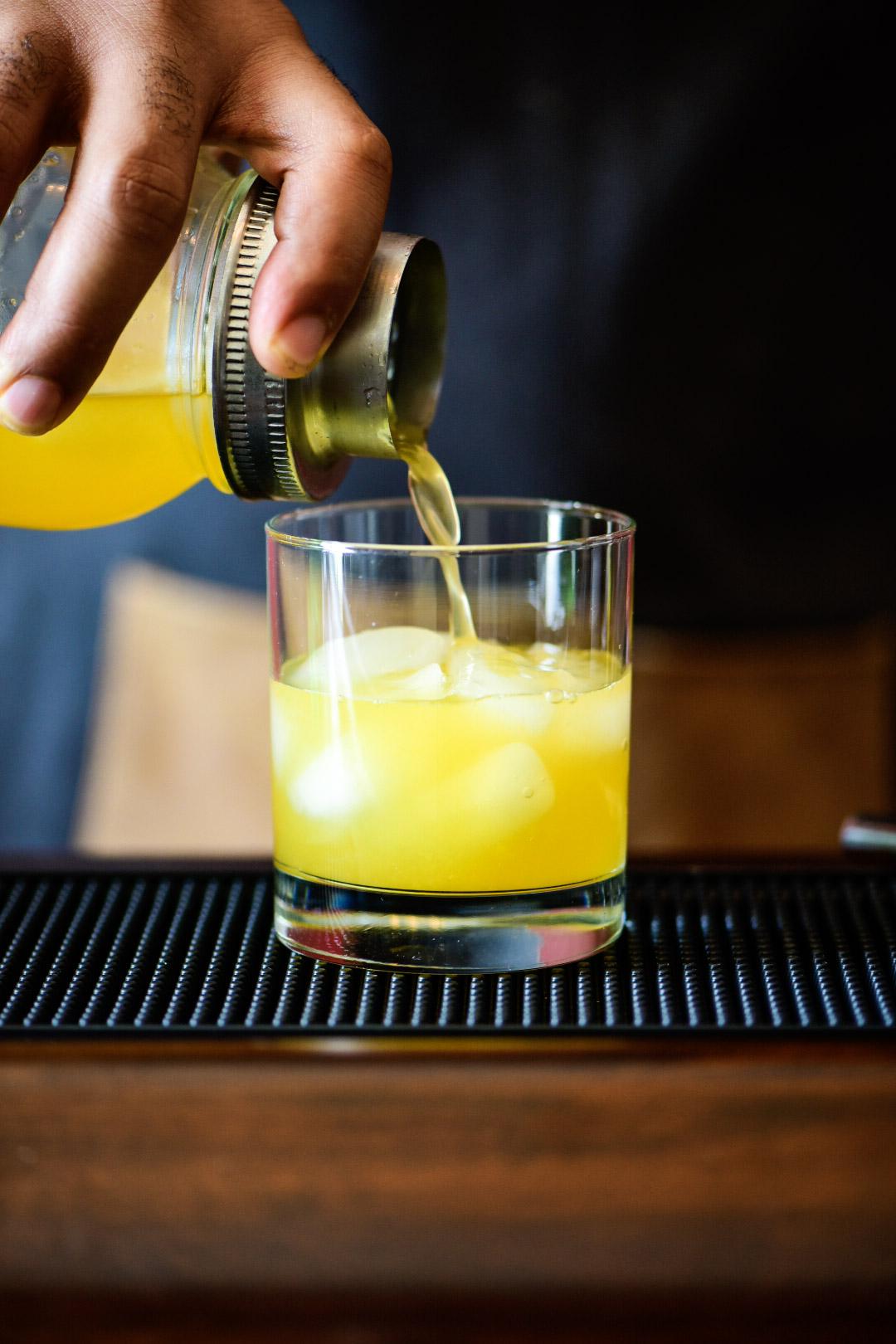 pouring shaken cocktail in iced glass for Mandarin Orange Crush Cocktail