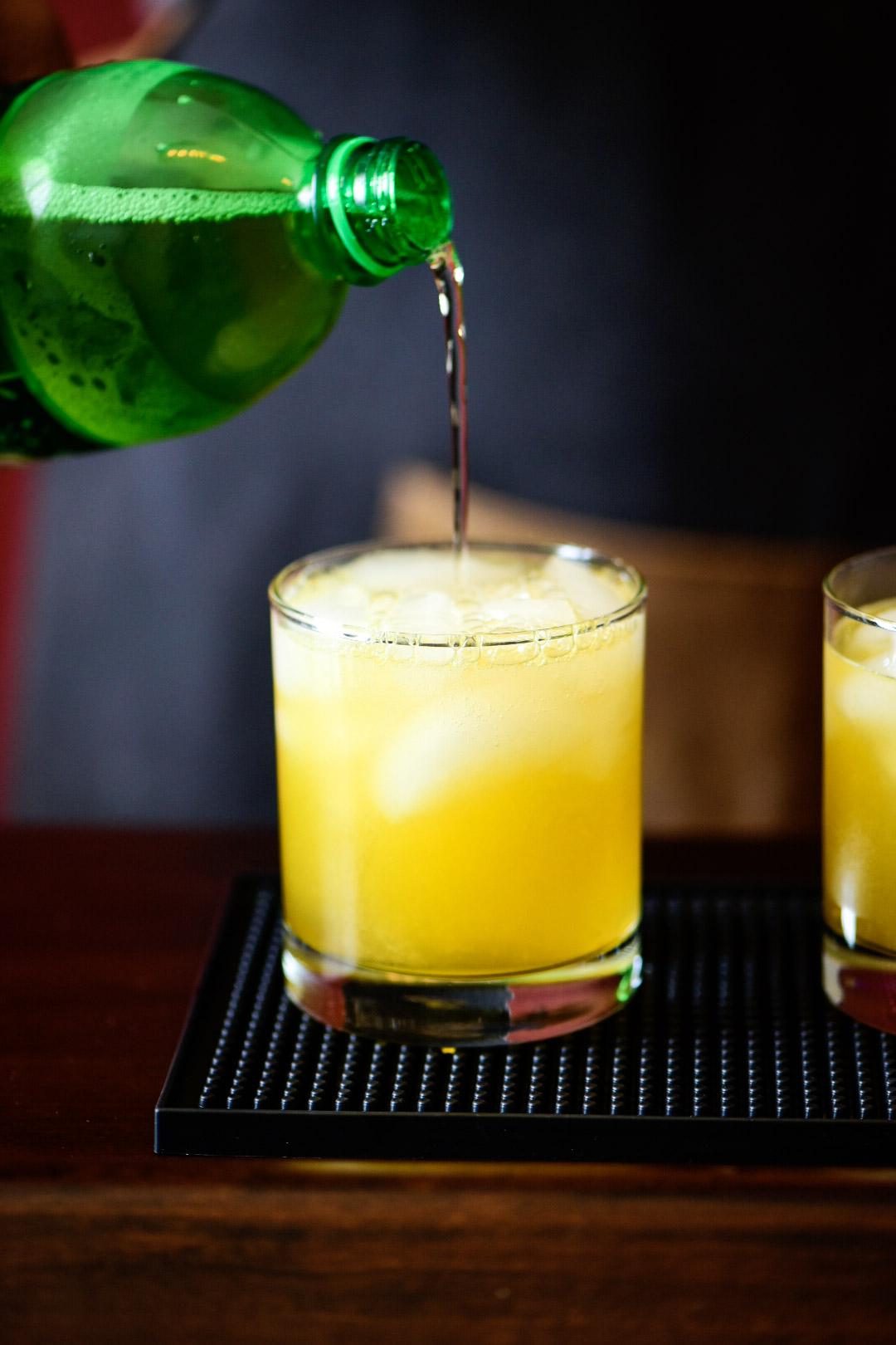 pouring soda or sparkling water for Mandarin Orange Crush Cocktail