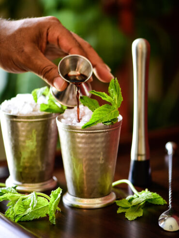 Topping off mint julep cocktail with blackberry liqueur