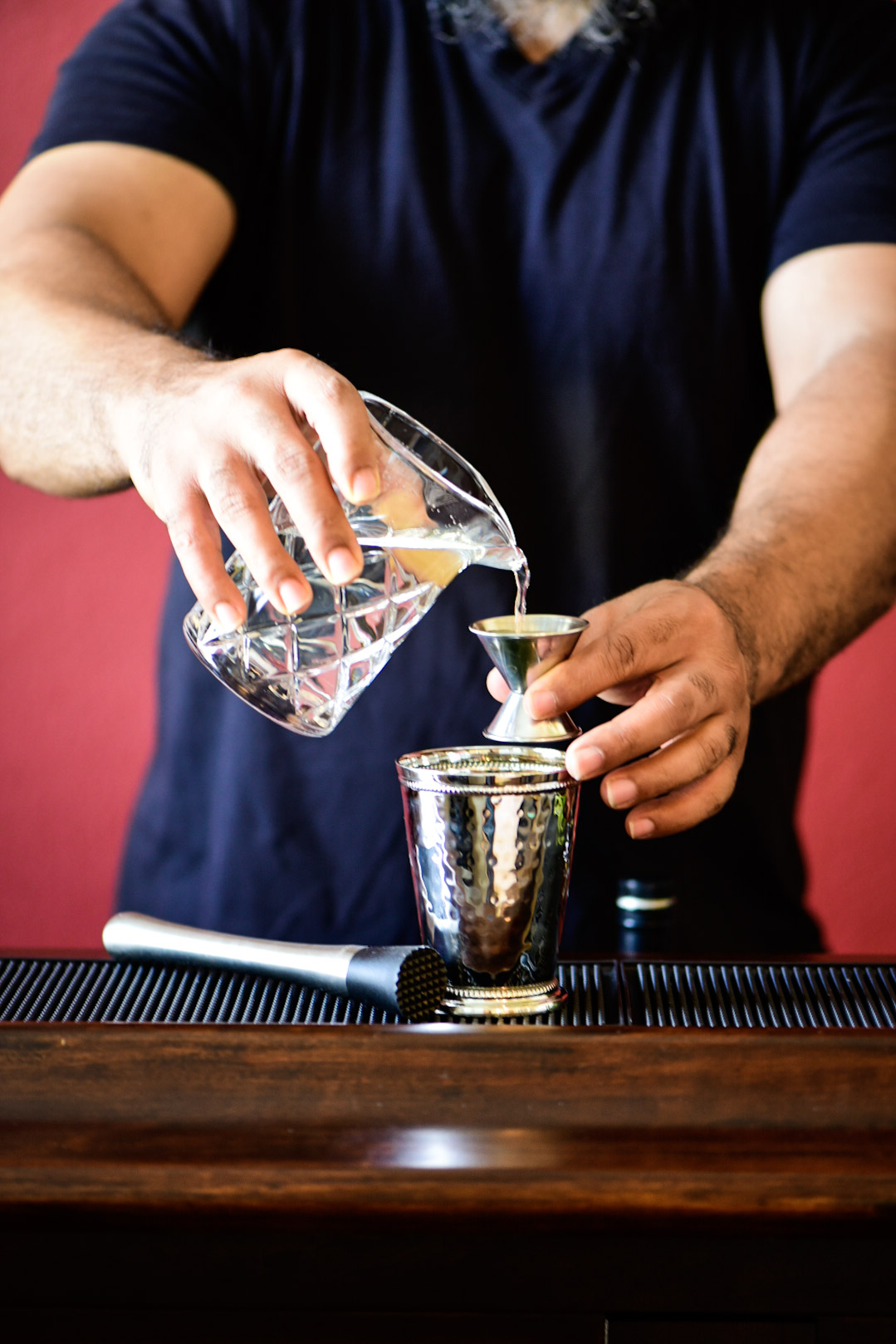 Pouring simple syrup into mint julep cup