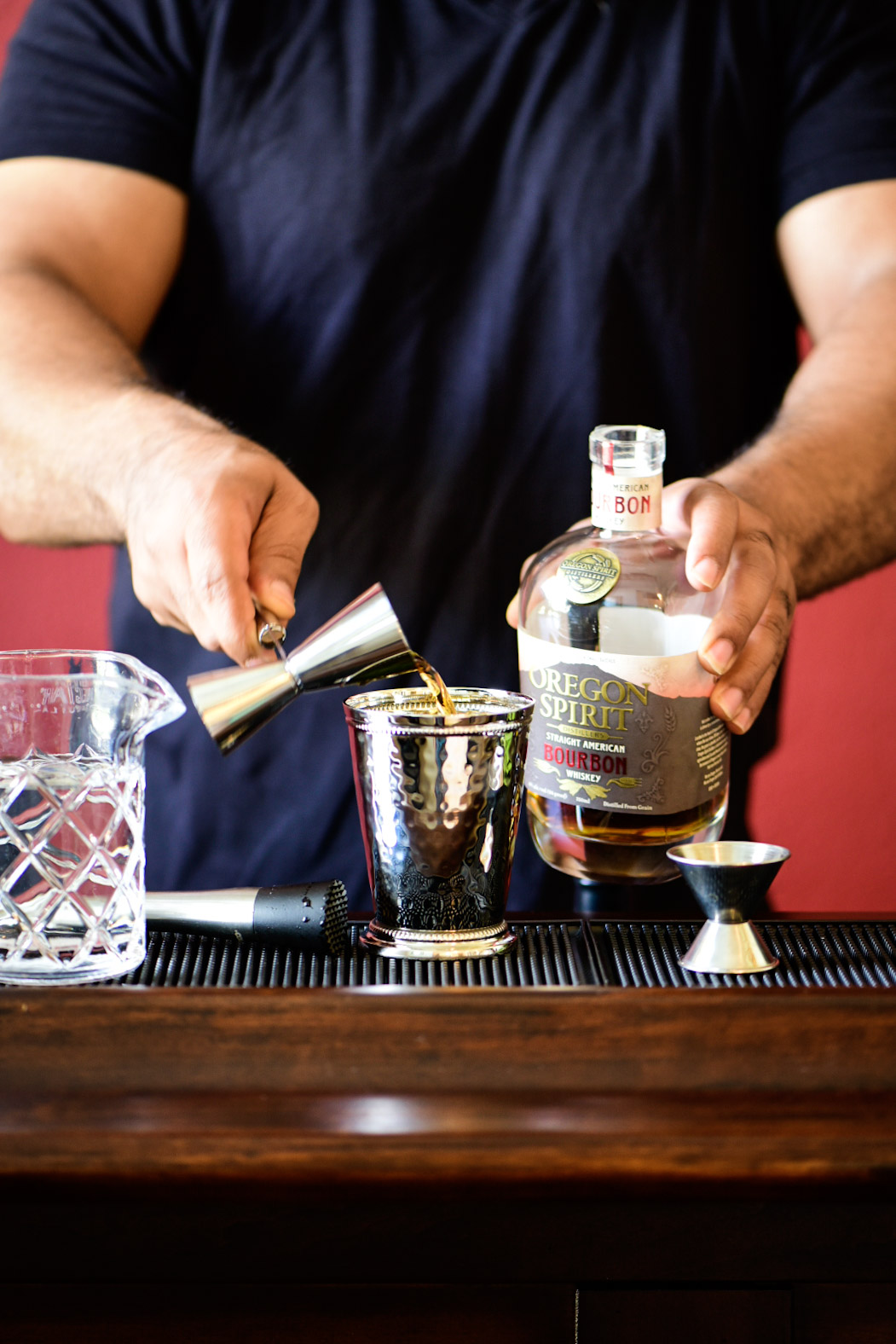 Pouring bourbon into mint julep cup