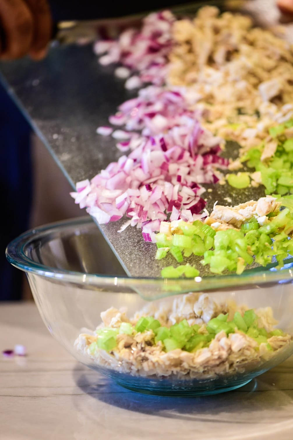 Adding chicken salad ingredients to a large bowl