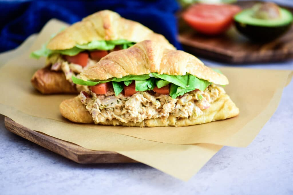 Chicken salad sandwich on a croissant with butter lettuce and tomato