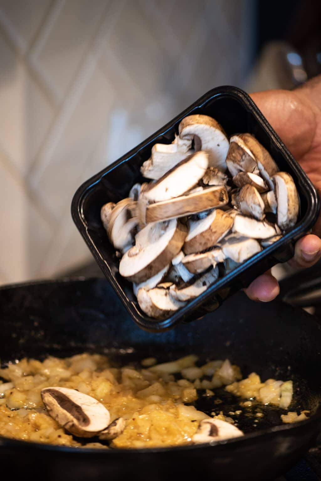 Adding fresh mushrooms to a skillet