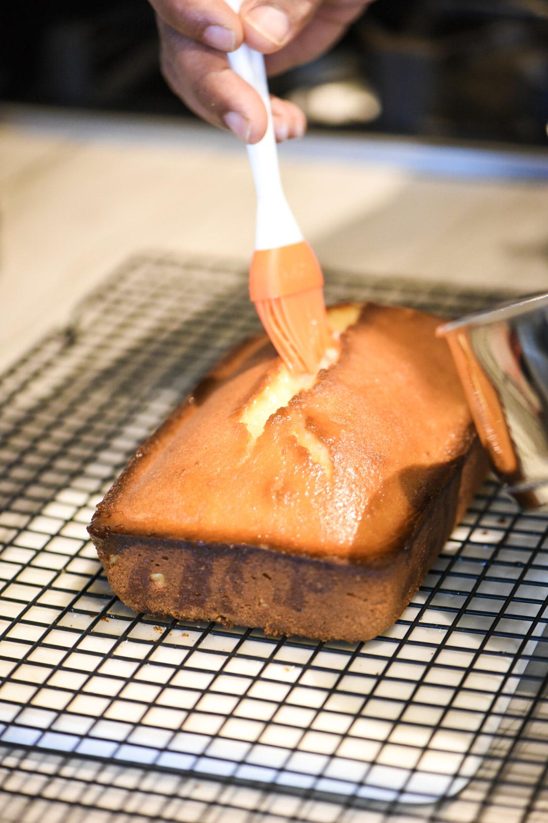 Brushing lemon syrup onto lemon pound cake