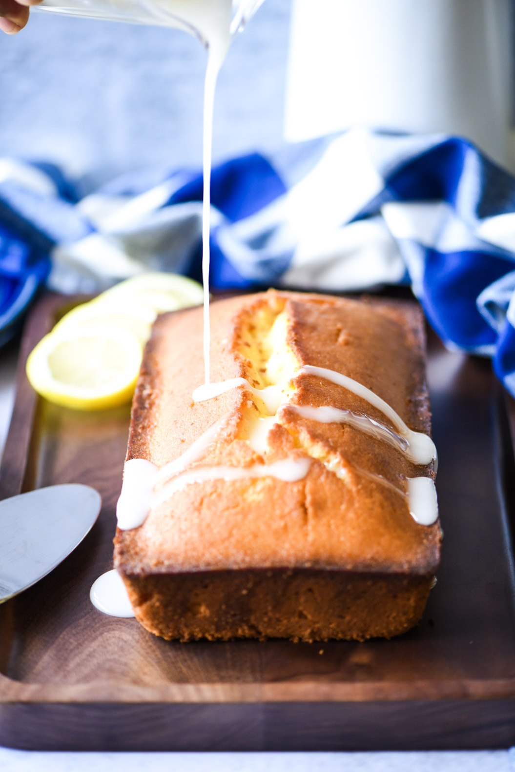 Pouring lemon glaze over the lemon pound cake