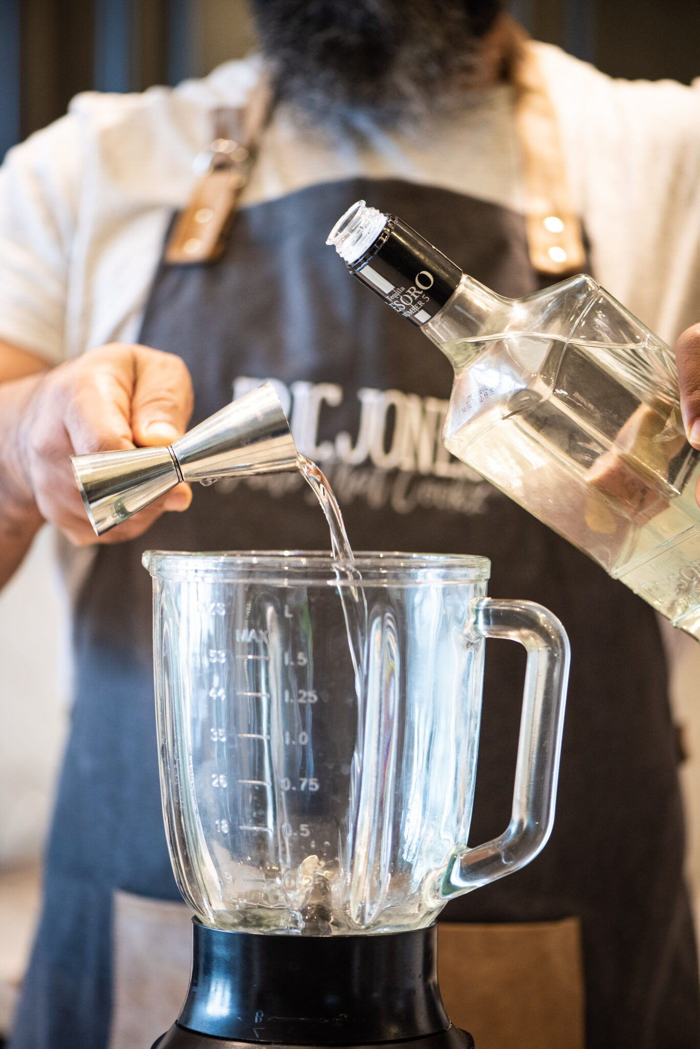 Pouring tequila in blender to make pear margarita