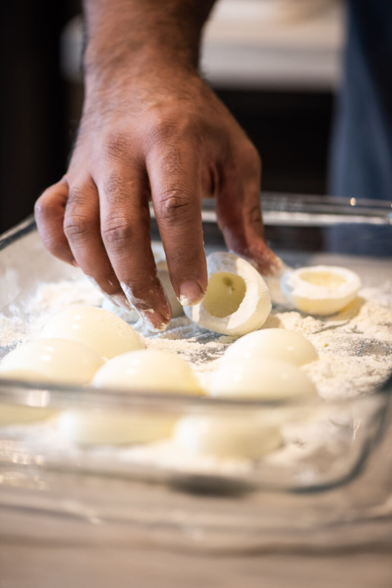 Flouring eggs to prepare to deep fry