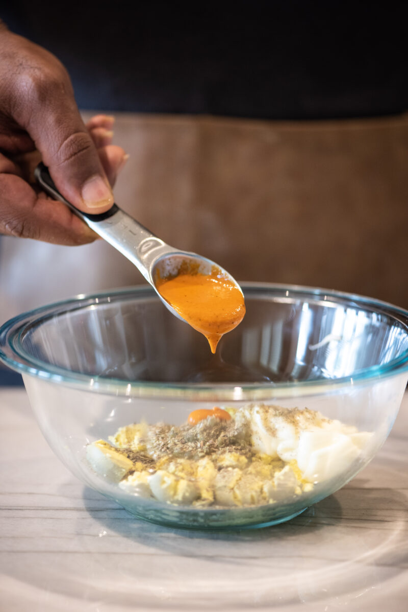 Adding buffalo sauce to deviled eggs mixture