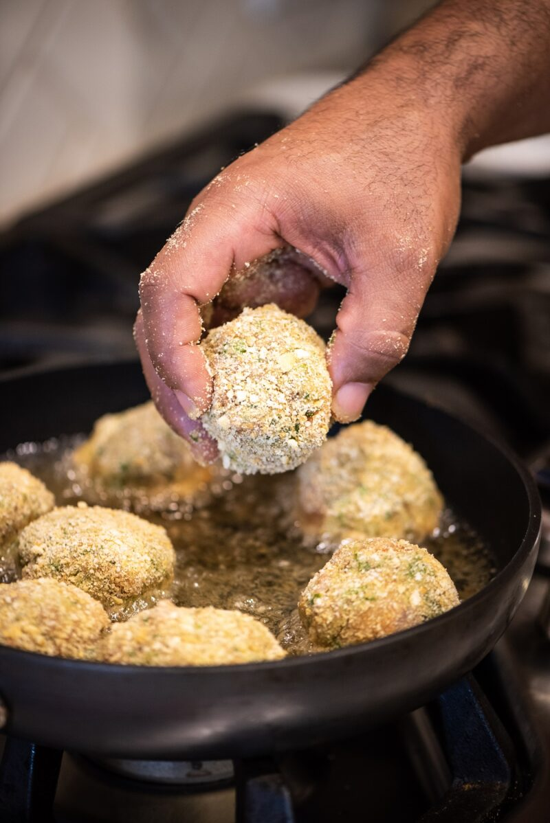 Placing croquettes into frying pan