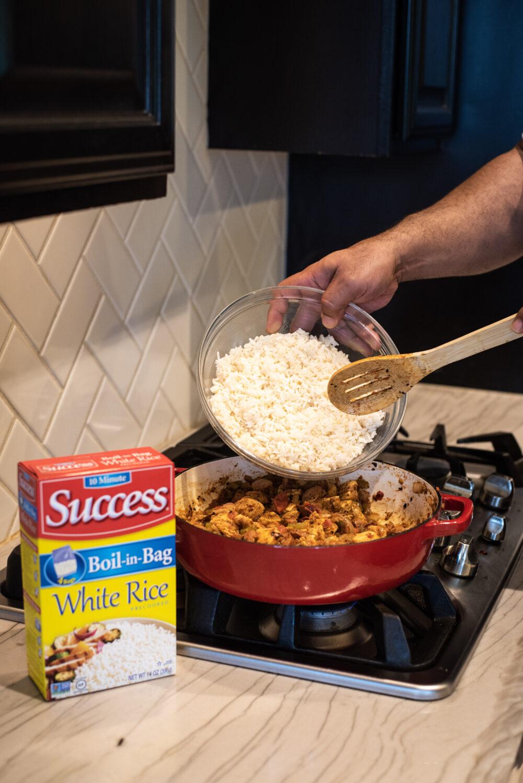Adding rice to jambalaya in cast iron skillet