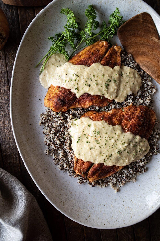 Overhead shot of baked flounder and pontchartrain sauce over quinoa