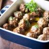 Close up shot of deep casserole dish of meatballs