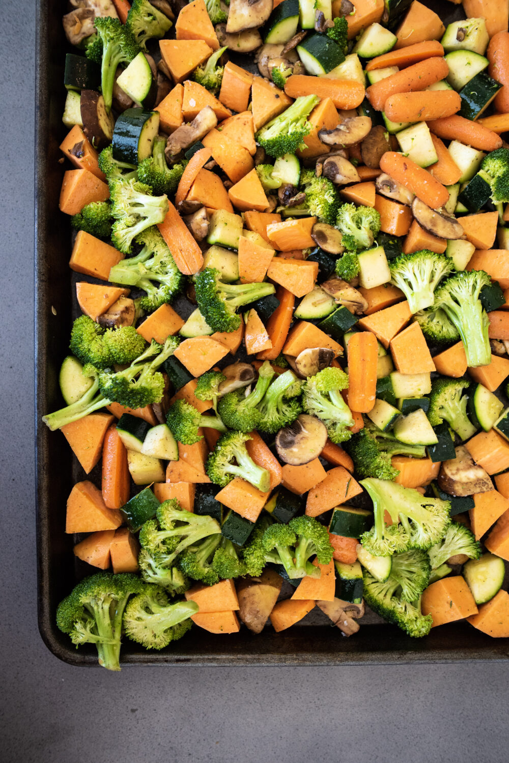 raw vegetables including carrots, mushrooms, sweet potatoes, and zucchini