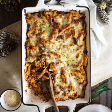 Overhead shot of baked ziti with wooden serving spoon