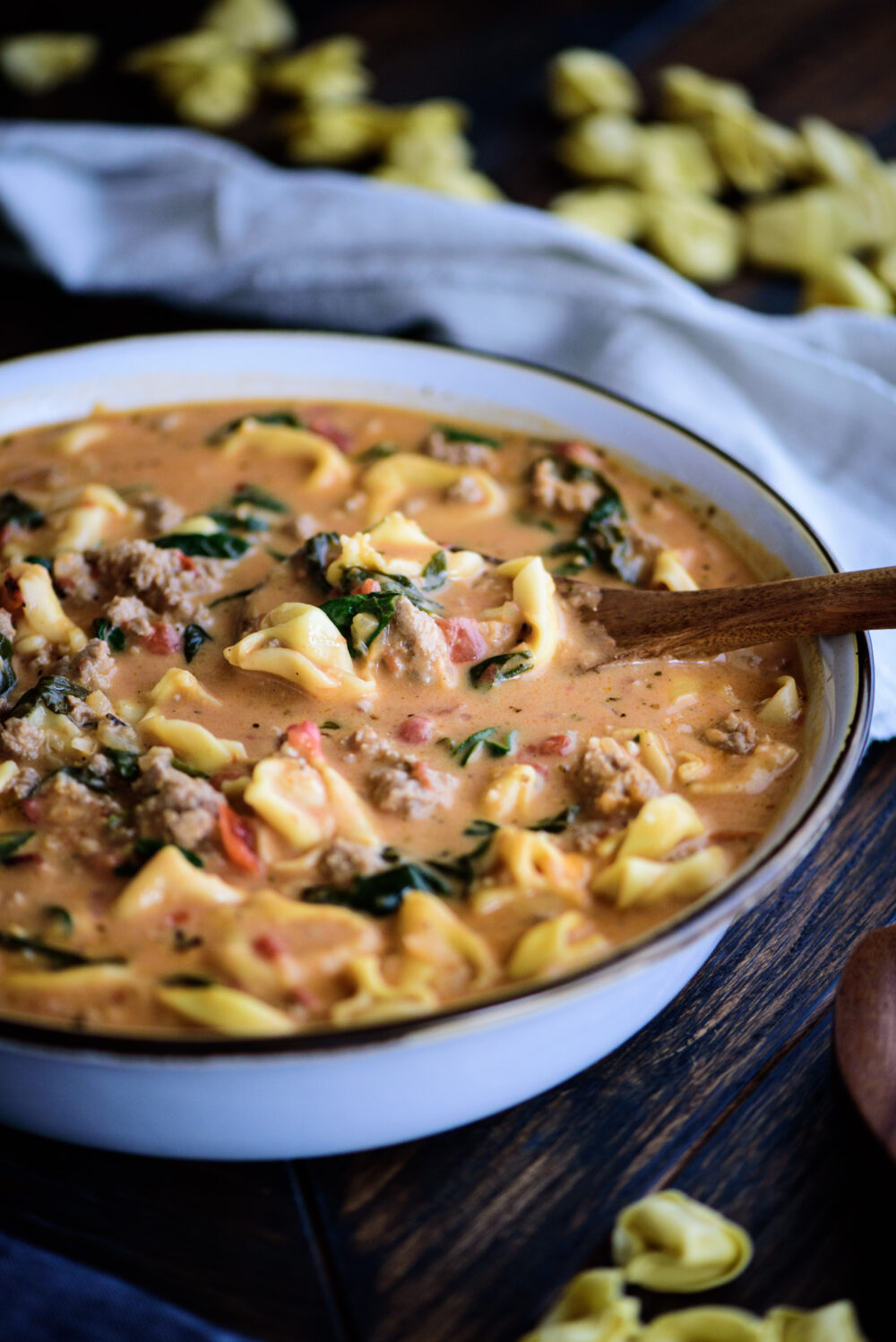 large bowl of tortellini soup with wooden serving spoon