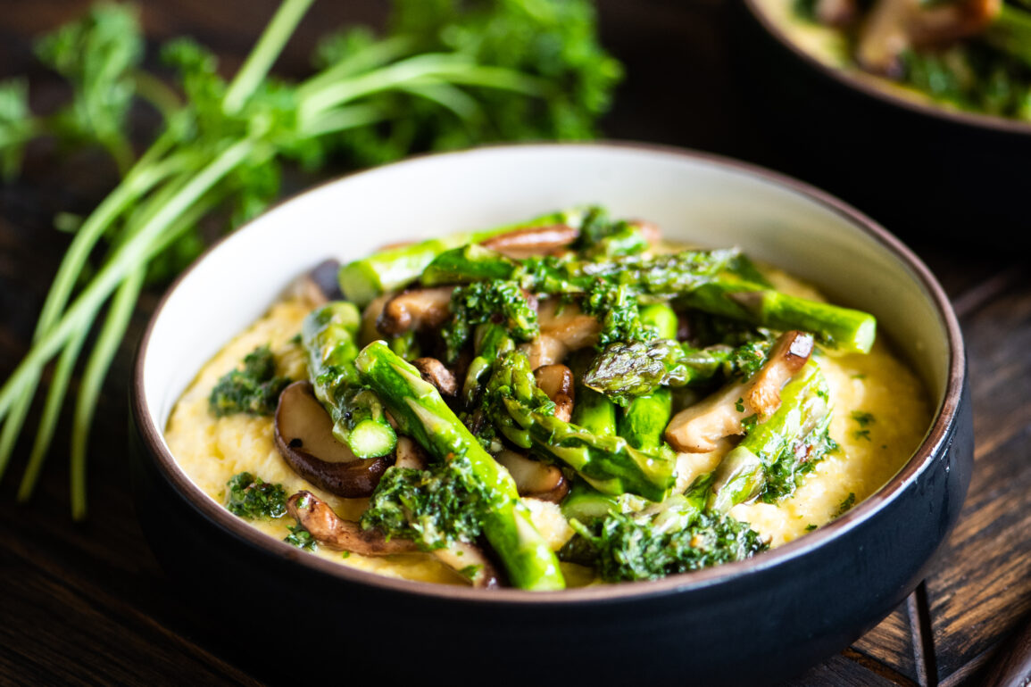 cheesy polenta and spring veggies surrounded by fresh mushrooms, asparagus, and parsley
