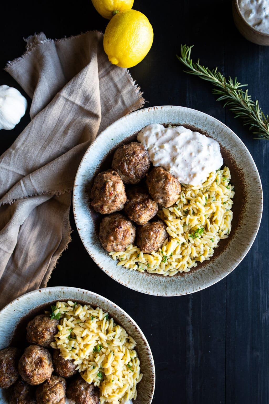 overhead shot of lamb meatballs, orzo, and tzatziki sauce
