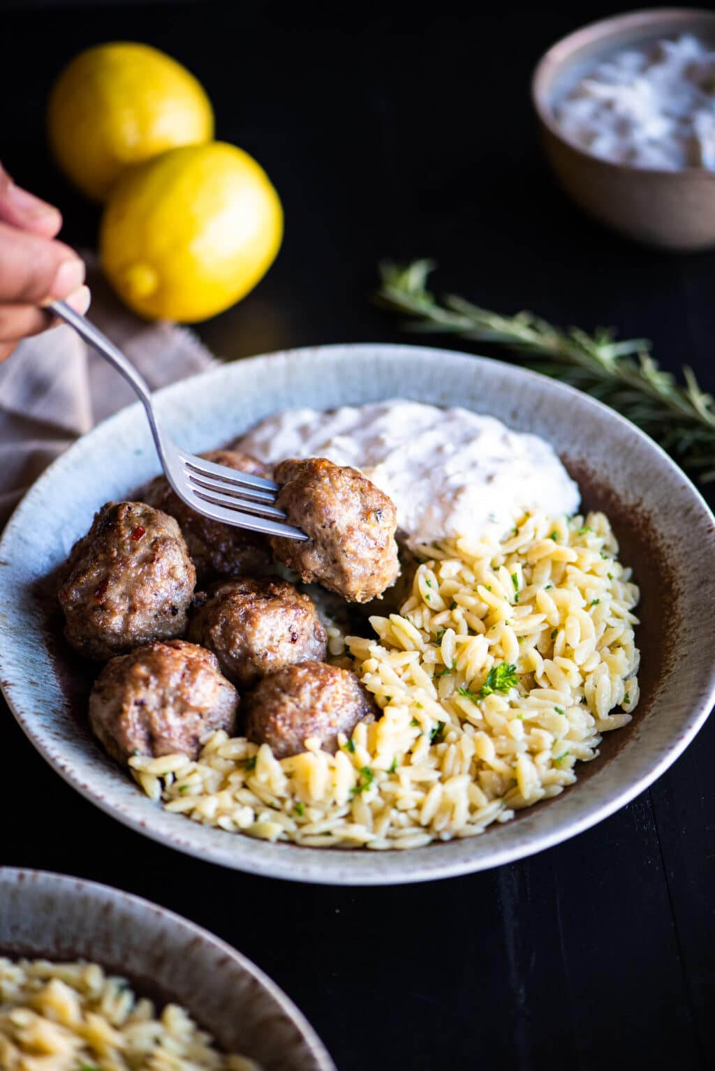 picking up a lamb meatball with a fork