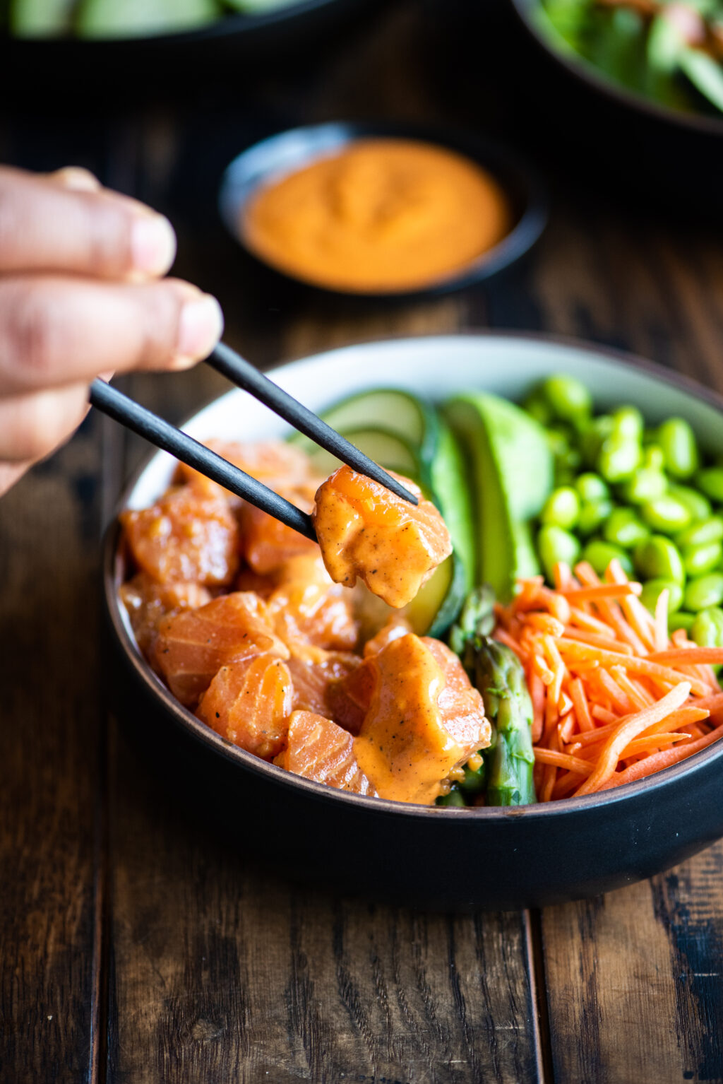 picking up a piece of salmon from the poke bowl