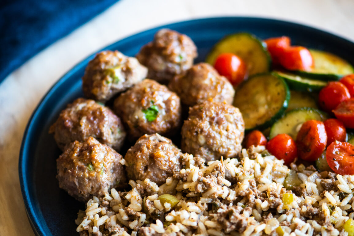 Plate of cajun meatballs, dirty rice, and a cucumber salad for meal prep