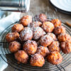 dusting powered sugar on the sweet potato fritters