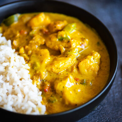 Close up of yellow fish curry served with white rice in a black bowl